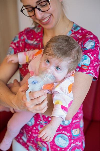Inhalující batole v náručí matky.